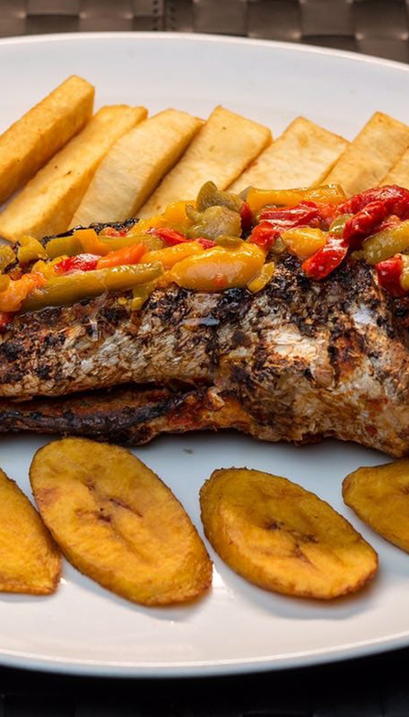 Grilled fish with plantain, fried yam and pepper sauce